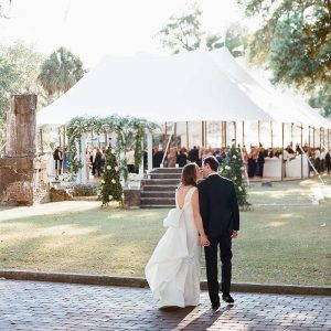 Wedding couple by outdoor reception tent